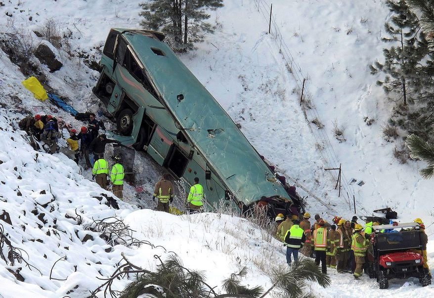 Emergency personnel respond to the scene of a multiple-fatality accident after a tour bus careened through a guardrail along an icy highway and fell several hundred feet down a steep embankment, authorities said, Sunday, Dec. 30, 2012 about 15 miles east of Pendleton, Ore. The charter bus carrying about 40 people lost control around 10:30 a.m. on the snow- and ice-covered lanes of Interstate 84, according to the Oregon State Police. (AP Photo/East Oregonian, Tim Trainor)