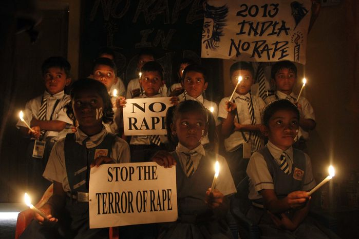 Indian schoolchildren hold candles and placards during a prayer ceremony in Ahmadabad, India, on Monday, Dec. 31, 2012, after the gang-rape and killing of a 23-year-old New Delhi physiotherapy student set off an impassioned debate about what India needs to do to prevent such a tragedy from happening again. (Associated Press)