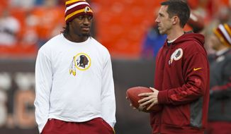 Washington Redskins quarterback Robert Griffin III, left, and offensive coordinator Kyle Shanahan, right, before an NFL football game against the Cleveland Browns in Cleveland, Sunday, Dec. 16, 2012. (AP Photo/Rick Osentoski)