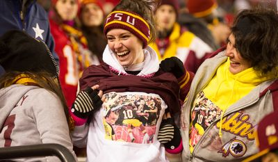 Prior to Sunday's game, Lauren Jones of DunKurk, Md., center, shows off her t-shirt she had made from another game that depicts Washington Redskins quarterback Robert Griffin III (10) jumping in the stands with her after a touchdown. (Andrew Harnik/The Washington Times)