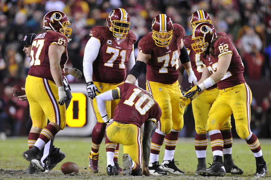 Washington Redskins quarterback Robert Griffin III (10) is slow to get up after being sacked in the fourth quarter at FedEx Field, Landover, Md., Dec. 30, 2012. (Preston Keres/Special to The Washington Times)