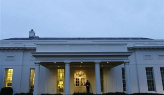 ** FILE ** A Marine sentry stands guard at the White House on Tuesday, Jan. 1, 2013, an indication that President Obama is working in the West Wing. (Associated Press)