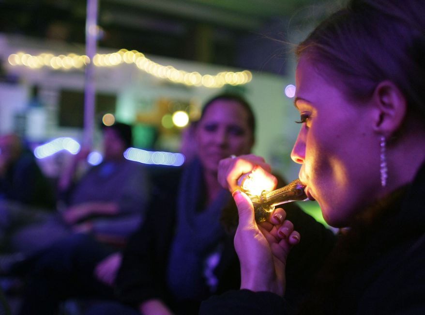 Rachel Schaefer of Denver smokes marijuana on the official opening night of Club 64, a marijuana-specific social club at which a New Year's Eve party was held, in Denver on Monday, Dec. 31, 2012. (AP Photo/Brennan Linsley)