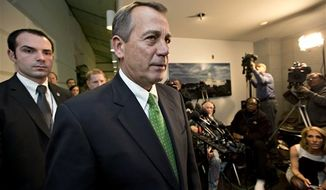 """Late on New Year's Day, Speaker of the House John A. Boehner, Ohio Republican, walks past reporters after a closed-door meeting meeting of House Republicans as the """"fiscal cliff"""" bill passed by the Senate last night waits for a vote in the GOP-controlled House, at the Capitol, Jan. 1, 2013. (AP Photo/J. Scott Applewhite)"""