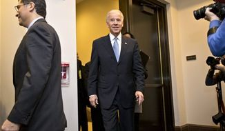Vice President Joseph R. Biden arrives for a closed-door meeting with House Democrats, on Capitol Hill, Tuesday, Jan. 1, 2013, to discuss the fiscal cliff bill passed by the Senate last night that's waiting for a vote in the Republican-controlled House. At left is Rep. Xavier Becerra, California Democrat. (AP Photo/J. Scott Applewhite)