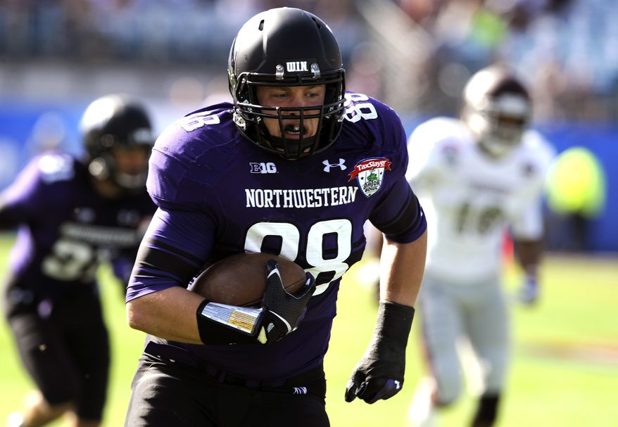 Northwestern defensive lineman Quentin Williams (88) returns a interception for a touchdown during the first half of the Gator Bowl NCAA college football game against Mississippi State, Tuesday, Jan. 1, 2013, in Jacksonville, Fla. (AP Photo/Stephen Morton)