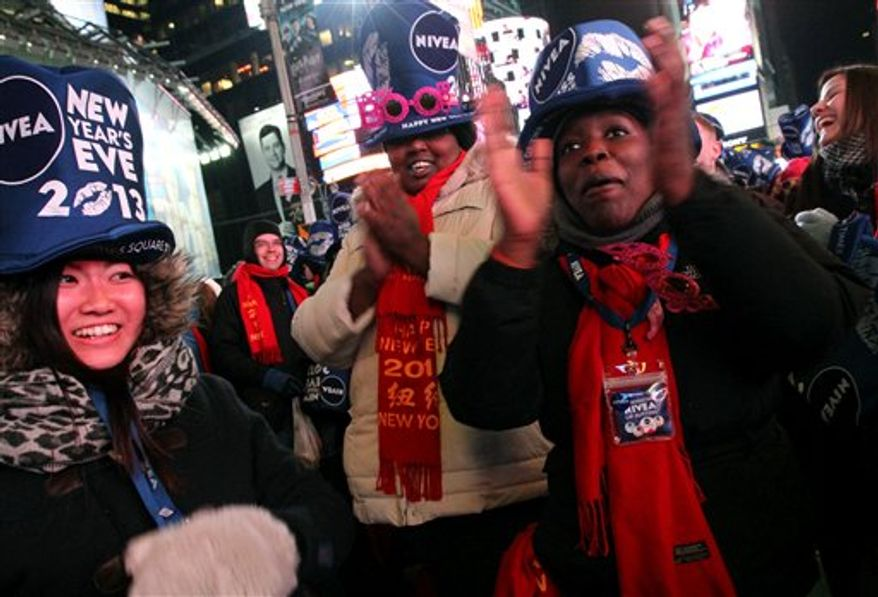 Yayoi Okayama, from Japan, left, Ziporah Choice, from New Jersey, foreground right, and others take part in the New Year's Eve festivities in New York's Times Square on Monday, Dec. 31, 2012. (AP Photo/Tina Fineberg)