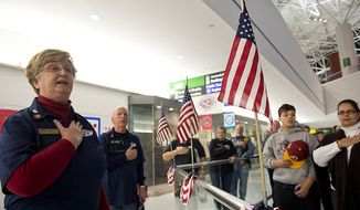 ** FILE ** Operation Welcome Home Maryland team leader Anne Church, left, leads volunteers and friends and family in the Pledge of Allegiance before the arrival of a Delta charter flight bringing troops home at BWI Thurgood Marshall Airport in Baltimore, Md., on Friday, Dec. 28, 2012. (Barbara L. Salisbury/The Washington Times)