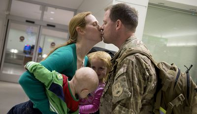 Holding her 10-month-old son Drew Jr. and 2 1/2-year-old daughter Lauren, Cheryl Lauer of Alexandria, Va. welcomes home her husband Drew after a six-month deployment in Qatar at BWI Thurgood Marshall Airport on Friday, Dec. 28, 2012. She said it has been really tough with the two little ones, since her husband left two weeks after she returned back to work from maternity leave. (Barbara L. Salisbury/The Washington Times)