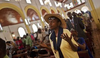 A churchgoer raises her hands as she prays for peace in the New Year's Day morning mass at the Notre Dame Cathedral of the Immaculate Conception in Bangui, Central African Republic on Jan. 1, 2013. President Francois Bozize's government is coming under growing threat as rebels vowing to overthrow him rejected appeals from the African Union to hold their advance and try to form a coalition government. (Associated Press)