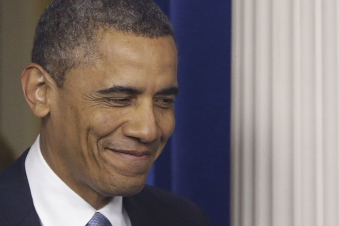 """President Obama smiles as he arrives in the Brady Press Briefing Room at the White House in Washington to make a statement regarding the passage of the """"fiscal cliff"""" bill on Tuesday, Jan. 1, 2013. (AP Photo/Charles Dharapak)"""