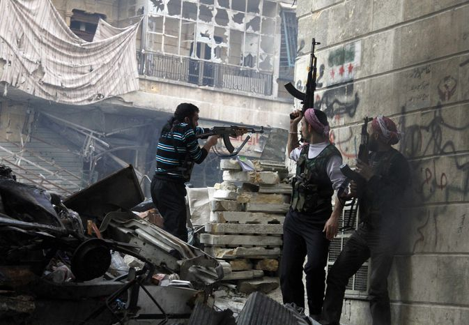 ** FILE ** In this Saturday, Dec. 29, 2012, photo, Free Syrian Army fighters fire at enemy positions during heavy clashes with government forces, in the Salaheddine district of Aleppo, Syria. Activists say Syrian rebels have captured an oil pumping station in the north central province of Raqqa about 160 km east of Aleppo after days of fighting. (AP Photo/Abdullah Al-Yasin)