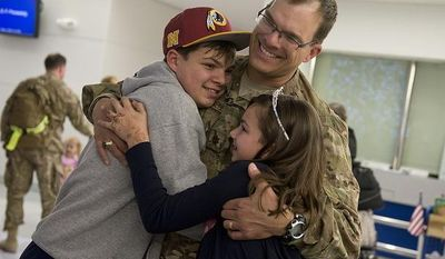 Charles and Caroline Brennikmeyer of Falls Church, Va. hug their dad, Maj. Oscar Brennikmeyer, U.S. Air Force, after he arrives on a military charter flight home from a six-month deployment in Afghanistan at BWI Thurgood Marshall Airport on Friday, Dec. 28, 2012. Friday was Charles' 14th birthday, and he said having his dad home was the best birthday gift ever. (Barbara L. Salisbury/The Washington Times)