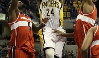 Indiana Pacers forward Paul George, center, shoots between Washington Wizards defenders Martell Webster, left, and Nene during the second half of an NBA game on Wednesday, Jan. 2, 2013, in Indianapolis. The Pacers won 89-81. (AP Photo/AJ Mast)
