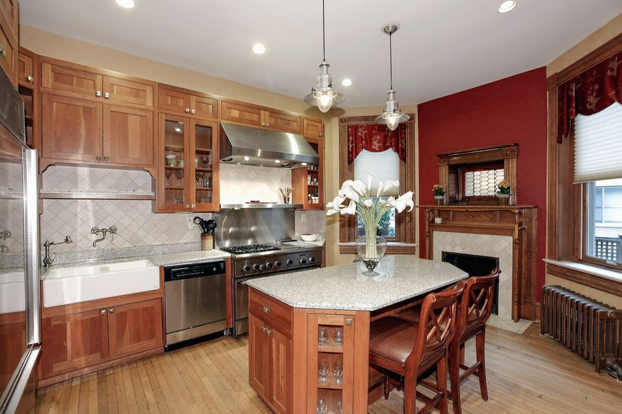 The kitchen has granite counters, stainless steel appliances and a large center island with room for seating. A fireplace is tucked underneath a stained-glass window and is flanked by two more tall windows.