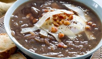 A lighter version of classic onion soup adds poached eggs. (Associated Press)