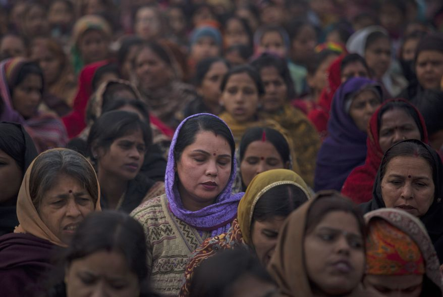 Indian women offer prayers for a gang-rape victim at the memorial to Mahatma Gandhi in New Delhi on Wednesday, Jan. 2, 2013. (AP Photo/Dar Yasin)