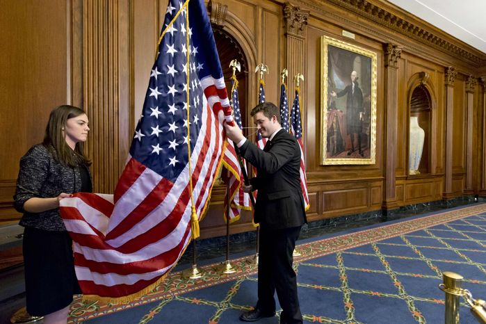 Anne Easby-Smith, left, and Trace Robbins, right, who work for House Speaker John Boehner, help to prepare the Rayburn Room on Capitol Hill in Washington, Wednesday, Jan. 2, 2013, where members of the House of Representatives will pose for pictures at an oath-of-office ceremony with Boehner. (AP Photo/J. Scott Applewhite)