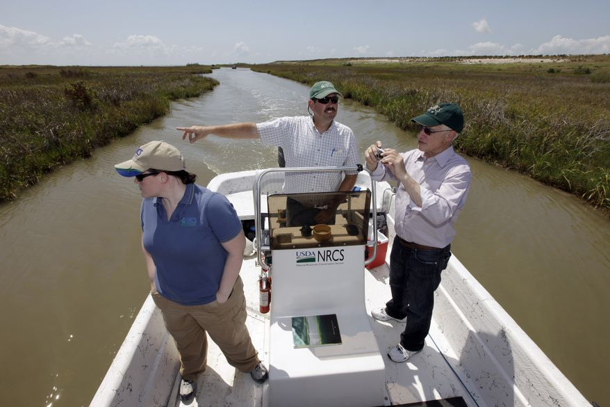 **FILE** Scott Alford (center), a soil conservationist for the Natural Resources Conservation Service, points out features of a man-made marsh to Harris Sherman (right), undersecretary for natural resources and the environment at the U.S. Department of Agriculture, and Julie Grogan-Brown (left), also with the USDA, near Baytown, Texas. The marsh is part of a project to restore lost wetlands and islands off the Texas coast. (Associated Press)