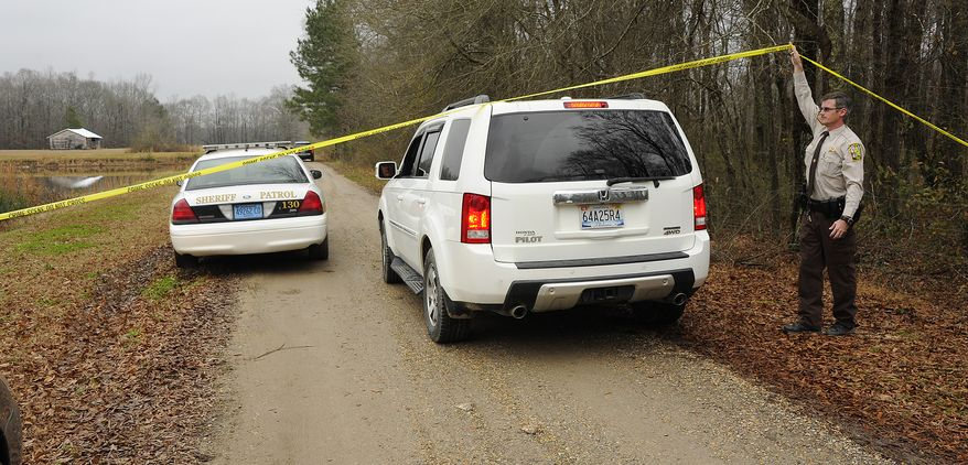 A Walker County sheriff's deputy lifts crime scene tape for investigators near Jasper, Ala., on Jan. 2, 2013, as National Transportation Safety Board officials continue investigate the fatal Jan. 1 crash of a small plane that was reported stolen. Walker County sheriff's Chief Deputy James Painter says authorities are still investigating but believe the teenagers took the plane without permission before it crashed that night. (Associated Press/AL.com)
