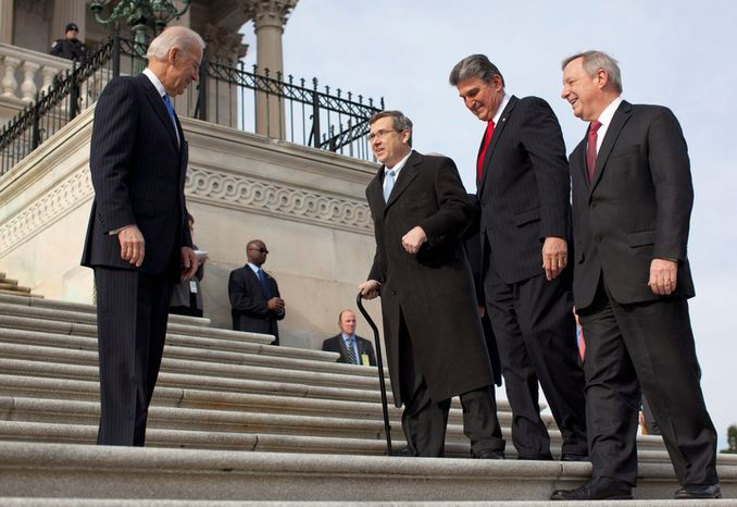 Vice President Joe Biden watches at left as Sen. Mark Kirk, R-Ill., second from left, accompanied by Sen. Joe Manchin, D-W.Va., second form right, and Senate Majority whip Richard Durbin of Ill., right, walks the steps to the Senate door of the Capitol building on Capitol Hill in Washington, Thursday, Jan. 3, 2013. Kirk said he often visualized climbing the 45 steps of the U.S. Capitol as a source of inspiration during his months of grueling physical therapy after suffering a major stroke last year.     (AP Photo/ Evan Vucci)
