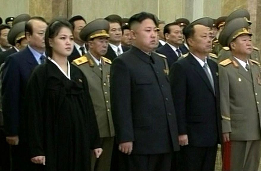 North Korean leader Kim Jong-un (second from left in front row) and his wife, Ri Sol-ju (left), attend a ceremony on Monday, Dec. 17, 2012, in Pyongyang, North Korea, to reopen the mausoleum where his father, Kim Jong-il's embalmed remains will lie in state, as North Koreans marked the first-year anniversary of the elder Kim's death. (AP Photo/KRT via AP Video)