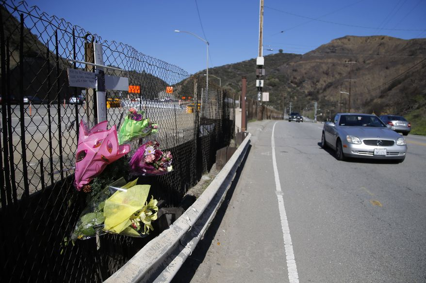 A roadside memorial marks the site at which paparazzo Christopher James Guerra was killed by a car while he darted across the street after taking pictures of singer Justin Bieber's Ferrari along the 405 freeway in Los Angeles on Wednesday, Jan. 2, 2013. (AP Photo/Jae C. Hong)