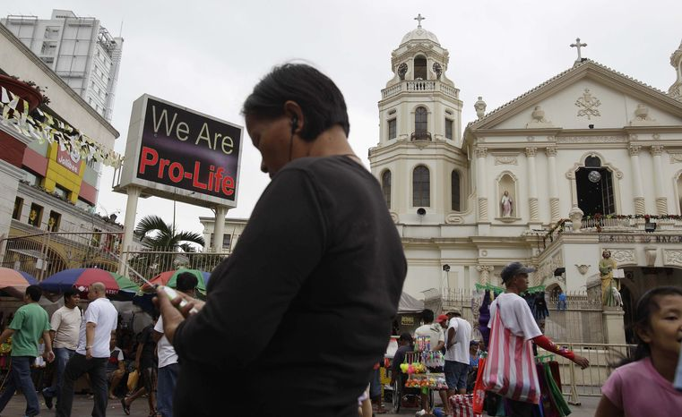 """A """"Pro-Life"""" message flashes on an electric signboard outside the Roman Catholic Minor Basilica of the Black Nazarene in downtown Manila on Thursday, Jan. 3, 2013. (AP Photo/Aaron Favila)"""