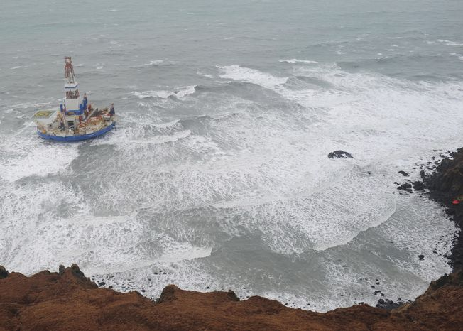 This aerial image provided by the U.S. Coast Guard shows the Royal Dutch Shell drilling rig Kulluk aground off a small island near Kodiak Island on Jan. 1, 2013. Officials said no leak has been seen from the drilling ship, which grounded off the island during a storm. (Associated Press/U.S. Coast Guard)