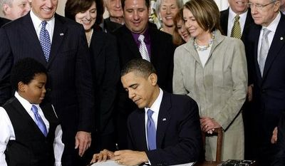 **FILE** President Obama signs the health care bill at the White House in Washington on March 23, 2010, flanked by smiling supporters from the House and Senate, and Vicki Kennedy (behind Mr. Obama's right shoulder), widow of Sen. Edward M. Kennedy, who was a champion of the legislation. (Associated Press)
