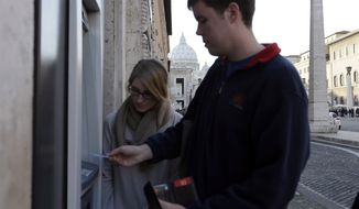 "Ben Kiniry of Texas gets cash from an ATM along Rome's Via della Conciliazione, the main street leading to the Vatican, on Thursday, Jan. 3, 2013. It's ""cash only"" now for tourists at the Vatican wanting to pay for museum tickets, souvenirs and other services after Italy's central bank decided to block electronic payments, including credit cards, in the tiny city-state. The dome of St. Peter's Basilica in the Vatican is in the background. (AP Photo/Alessandra Tarantino)"