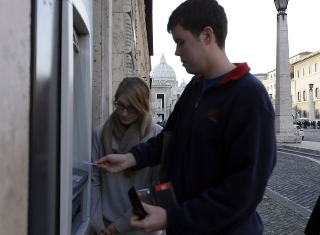 """Ben Kiniry of Texas gets cash from an ATM along Rome's Via della Conciliazione, the main street leading to the Vatican, on Thursday, Jan. 3, 2013. It's """"cash only"""" now for tourists at the Vatican wanting to pay for museum tickets, souvenirs and other services after Italy's central bank decided to block electronic payments, including credit cards, in the tiny city-state. The dome of St. Peter's Basilica in the Vatican is in the background. (AP Photo/Alessandra Tarantino)"""