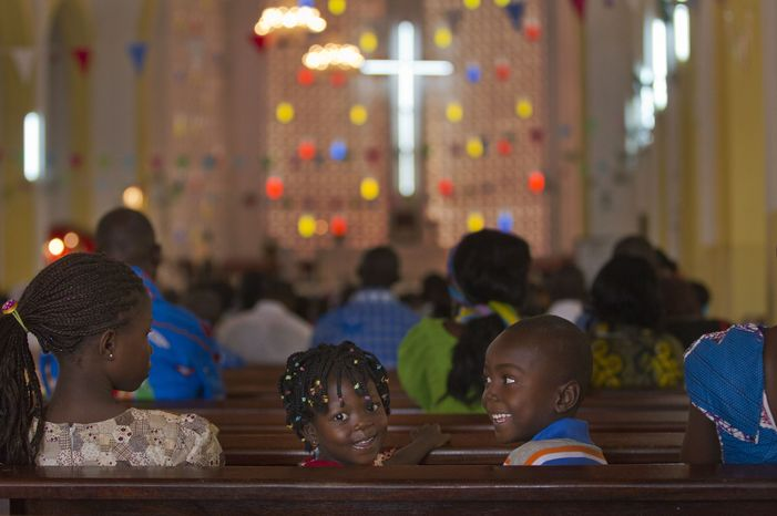 Two children sitting on a church pew look back as a New Year's Day morning mass is conducted at the Notre Dame Cathedral of the Immaculate Conception in Bangui, Central African Republic, on Jan. 1, 2013. (Associated Press)