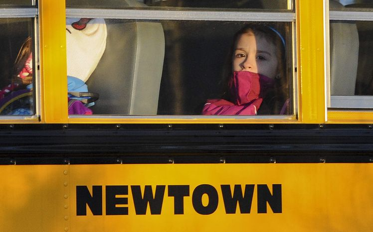 **FILE** A girl sits on a Newtown bus leaving the new Sandy Hook Elementary School after the first day of classes in Monroe, Conn., on Jan. 3, 2013. The Sandy Hook students started that day in their new school, formerly called Chalk Hill School in Monroe. It was renamed Sandy Hook Elementary and overhauled especially for the students from the Sandy Hook School shooting. (Associated Press)
