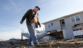 Henny Mauro walks in Seaside Heights, N.J., on Jan. 3, 2013, past a beach-side home that was destroyed by Superstorm Sandy. (Associated Press)
