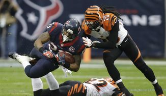 Houston Texans running back Arian Foster (23) is tackled by Cincinnati Bengals free safety Reggie Nelson (20) during the second quarter of an NFL wild card playoff football game Saturday, Jan. 5, 2013, in Houston. Cincinnati Bengals strong safety Nate Clements is underneath Foster. (AP Photo/Eric Gay)