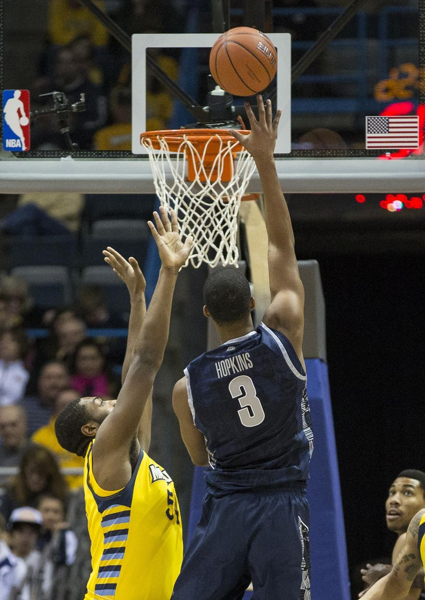 Marquette's Davante Gardner, left, defends as Georgetown's Mikael Hopkins shoots during the first half of an NCAA college basketball game Saturday, Jan. 5, 2013, in Milwaukee. (AP Photo/Tom Lynn)