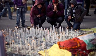 An Indian family lights candles in memory of a gang-rape victim in New Delhi, India, Saturday, Jan. 5, 2013. Passers-by refused to stop to help a naked, bleeding gang-rape victim after she was dumped from a bus onto a New Delhi street, and police delayed taking her to a hospital for 30 minutes, the woman's male companion said in an interview. (AP Photo/Altaf Qadri)