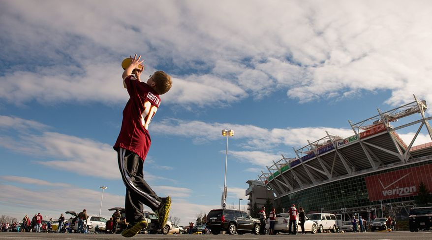 Andrew harnik/the washington times  Jackson Clarke, 11, of Sterling, Va., tosses a football in the parking lot before the Washington Redskins playoff game with the Seattle Seahawks at FedEx Field in Landover, Md., on Sunday.