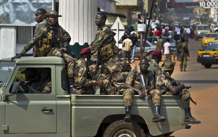 Government security forces in a pickup truck drive past a demonstration by several hundred merchants calling for peace on Saturday, Jan. 5, 2013, in downtown Bangui, Central African Republic, as negotiators prepare for talks with rebels from the north. (AP Photo/Ben Curtis)