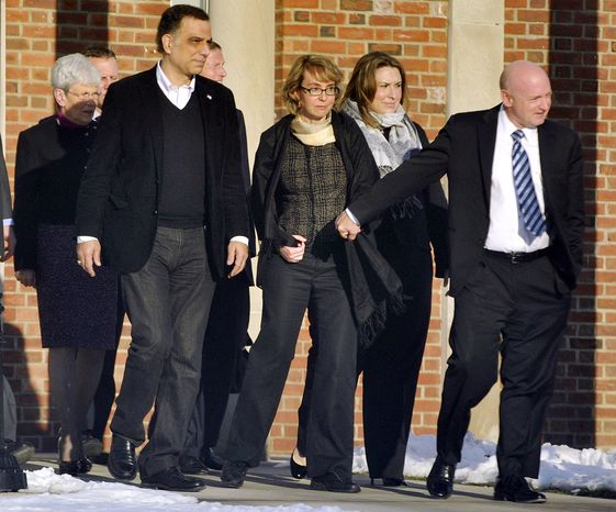 Former Rep. Gabrielle Giffords (third from right), holds hands with her husband, Mark Kelly (right), while leaving Town Hall at Fairfield Hills Campus in Newtown, Conn., after meeting with Newtown First Selectman Pat Llodra and other officials on Friday, Jan. 4, 2013. At far left is Connecticut Lt. Gov. Nancy Wyman; behind Mrs. Giffords to the left is Sen. Richard Blumenthal, Connecticut Democrat. Mrs. Giffords also met with families of the victims of the Sandy Hook Elementary School massacre that left 26 people dead. (AP Photo/The News-Times, Jason Rearick)
