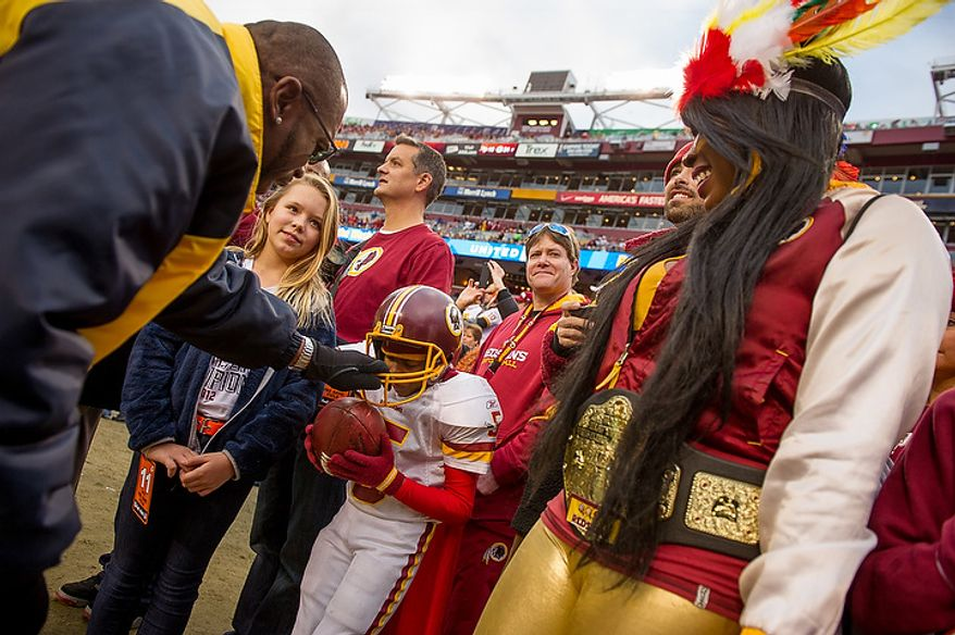 "Redskins fan Cookie Chiesette [cq], right, of Washington, D.C., watches as Security guard Derrick Jones, left, teases her son Davey ""Skins"", center, as they stand on the sideline before the Washington Redskins play the Seattle Seahawks during the NFC wild card game at FedEx Field, Landover, Md., Sunday, January 6, 2013. (Andrew Harnik/The Washington Times)"