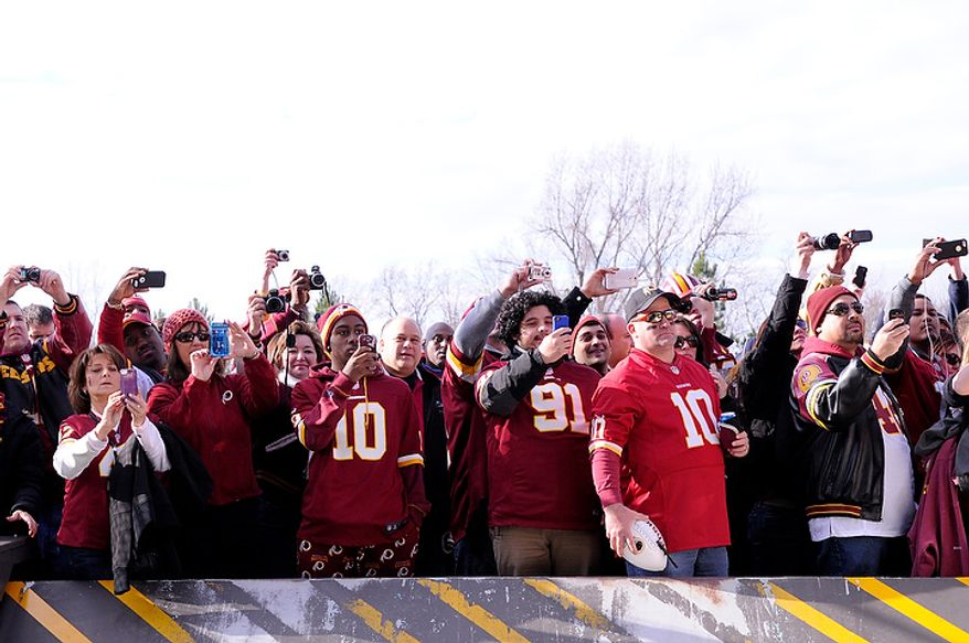Fans stand outside the stadium as they watch the Redskins arrive at FedEx Field, Landover, Md., Jan. 6, 2013. (Preston Keres/Special to The Washington Times)