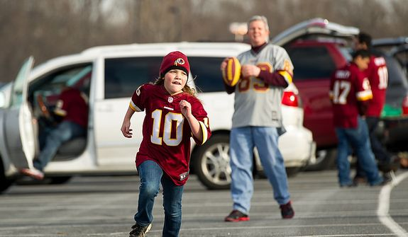 Jeff Clarke of Sterling, Va., throws passes to his daughter Katherine, 8, in the parking lot before the Washington Redskins play the Seattle Seahawks on wildcard weekend in NFL playoff football at FedEx Field, Landover, Md., Sunday, January 6, 2013. (Andrew Harnik/The Washington Times)