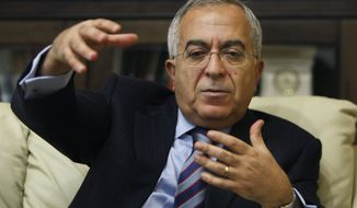 Palestinian Prime Minister Salam Fayyad gestures during an interview with The Associated Press in the West Bank city of Ramallah, on Sunday, Jan. 6, 2013. Mr. Fayyad blames Arab countries that haven't delivered promised financial aid for an escalating financial crisis in the Palestinian territories. (AP Photo/Majdi Mohammed)