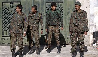 Yemeni soldiers stand guard outside a state security court during a trial of suspected al Qaeda militants in Sanaa, Yemen, on Sunday, Jan. 6, 2013. Yemen's state security court has sentenced five people to up to 10 years in prison for carrying out attacks against security forces and supporting the group logistically in the southern province of Abyan in 2011. (AP Photo/Hani Mohammed)
