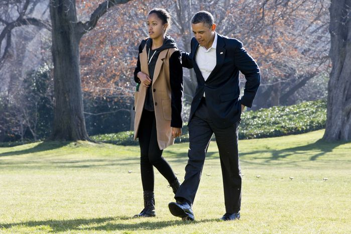 President Obama walks across the South Lawn of the White House with daughter Malia on Sunday, Jan. 6, 2013, after the first family's return to Washington from a vacation in Hawaii. (AP Photo/Jacquelyn Martin)