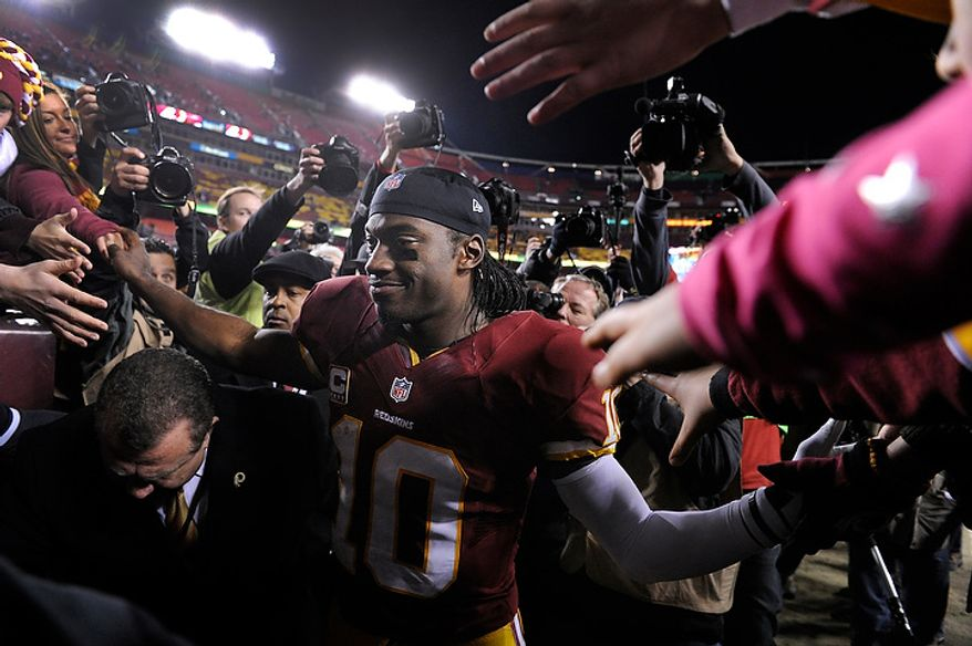 Washington Redskins quarterback Robert Griffin III (10) is greeted by fans as he leave the field after a loss in the NFC wild card game at FedEx Field, Landover, Md., Jan. 6, 2013. (Preston Keres/Special to The Washington Times)