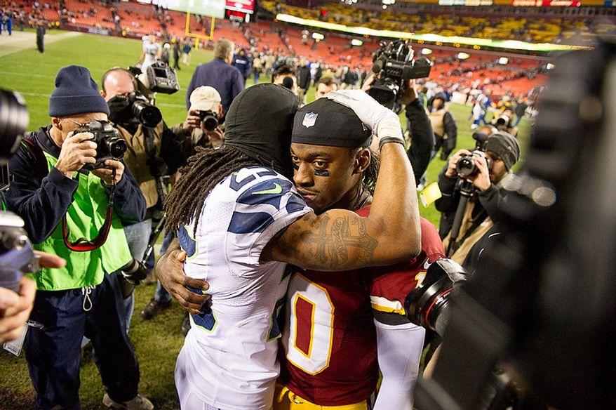 Seattle Seahawks cornerback Richard Sherman (25) gives Washington Redskins quarterback Robert Griffin III (10) a hug after the Washington Redskins lose to the Seattle Seahawks 24-14 in the NFC wild card game at FedEx Field, Landover, Md., Sunday, January 6, 2013. (Andrew Harnik/The Washington Times)