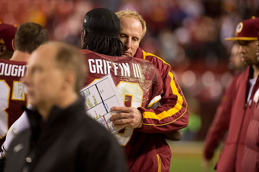 Washington Redskins quarterback Robert Griffin III (10) gets a hug from Washington Redskins defensive coordinator Jim Haslett after leaving the game with an injured knee late in the fourth quarter as the Washington Redskins play the Seattle Seahawks during the NFC wild card game at FedEx Field, Landover, Md., Sunday, January 6, 2013. (Andrew Harnik/The Washington Times)